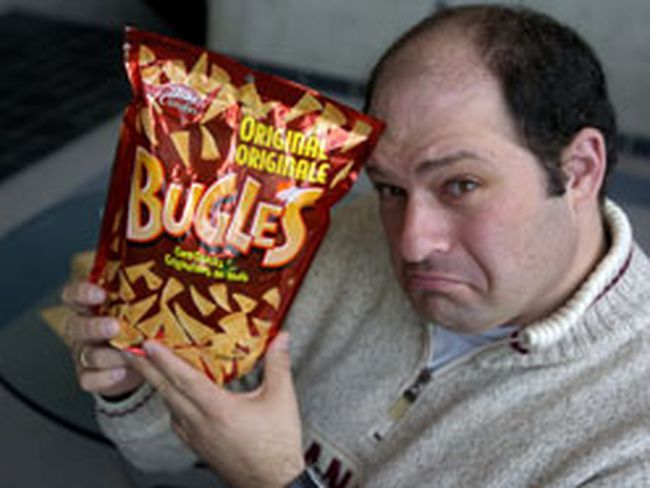 Laurence Simner holds a bag of his beloved Bugles, which are no longer available in Canada. (Sue Reeve, The London Free Press)