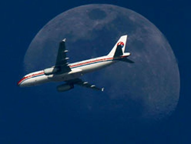 A China Eastern Airlines passenger jet passes in front of the moon over Shanghai in this May 13, 2011 file photograph. (REUTERS/Aly Song/Files)