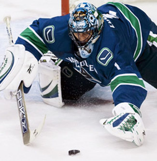 Vancouver Canucks' goalie Roberto Luongo reaches for the loose puck during first period of NHL play against the Calgary Flames in Vancouver, British Columbia October 9, 2008. (REUTERS)