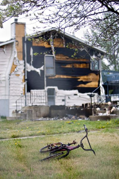 A burnt child's bike lays on the grass under a living tree in front of a completely decimated home in Slave Lake, Alta., on Friday, May 27 2011. (AMBER BRACKEN/ EDMONTON SUN)