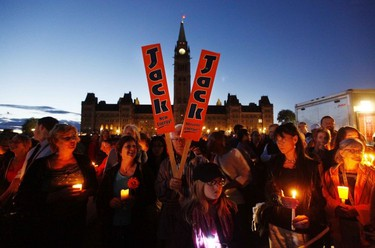 Members of the public gather at the Centennial Flame on Parliament Hill to mourn the loss of the late Jack Layton Leader of the New Democratic Party during a candle lit vigil, in Ottawa, August 22, 2011.(Chris Roussakis/QMI Agency)