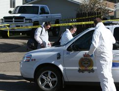 Medicine Hat forensics team gets suited up Monday morning to go into the house on Cameron Road in Medicine Hat where a family was slain. (File photo THE CALGARY SUN)