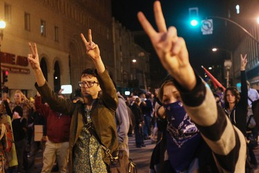 """A group of """"Occupy Wall Street"""" demonstrators gesture peace signs toward a line of police officers during a protest in response to an early morning police raid which displaced Occupy Oakland's tent city in Oakland, California October 25, 2011. (REUTERS/Stephen Lam)"""