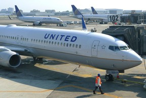 A ground crew member walks past a United Airlines airplane as it sits at a gate at Newark Liberty International Airport in Newark, New Jersey, June 18, 2011.  REUTERS/Gary Hershorn