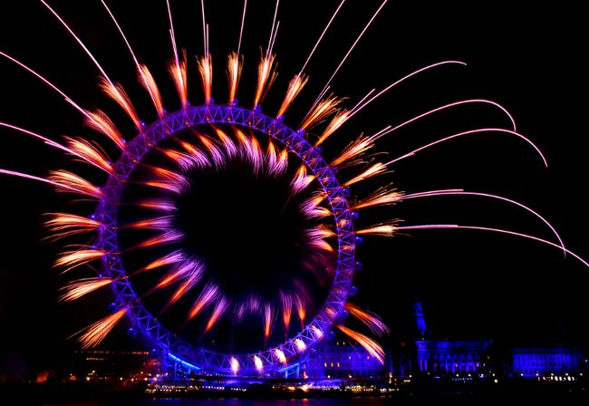 <b>London, England:</b> More than a quarter-million people flock to the shores of the Thames River for the annual New Year's Eve party in London. The iconic bells of Big Ben sound at midnight as fireworks are launched from the London Eye. (Shutterstock)