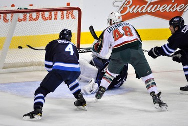 Minnesota Wild Guillaume Latendresse (48) gets past Winnipeg Jets defenders Zach Bogosian (4) and Mark Stuart (R) to score on goaltender Ondrej Pavelec (31) during the second period of their NHL hockey game in Winnipeg on Tuesday, Dec. 13, 2011. (REUTERS/Fred Greenslade)