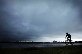 A cyclist rolls along the Ottawa River Parkway bicycle path just as a storm rolls across the Ottawa River into Ottawa from Quebec Friday, June 24, 2011. Rain is expected to continue through the weekend.  (DARREN BROWN/OTTAWA SUN)