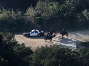 LAPD mounted police officers search a hilly area below the iconic Hollywood sign in Los Angeles, California January 18, 2012. (REUTERS/Jonathan Alcorn)