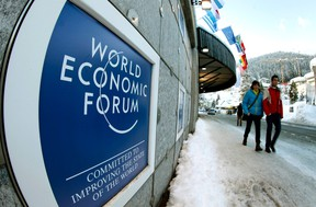 People walk past the logo of the World Economic Forum (WEF) in front of the congress center in the Swiss mountain resort of Davos January 22, 2012. The WEF takes part at the congress center from January 25 to 29.    REUTERS/Arnd Wiegmann
