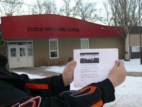 """Rachael Friesen holds a copy of the Ally pledge — which says, among other things, """"I support lesbian, gay, bisexual, transgender, Two-Spirit, intersex, queer and questioning individuals, families and communities"""" — in front of West Park School in Altona, Man., in January 2012. Friesen is among a group parents upset the school has told a Grade 5 teacher to take down the pledge on the grounds it isn't age-appropriate. (LORI PENNER/Red River Valley Echo)"""