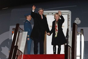 Canada's Prime Minister Stephen Harper and his wife Laureen wave while disembarking their plane after arriving in Beijing February 7, 2012. REUTERS/Chris Wattie