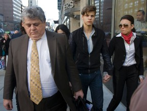Oliver Karafa, 19 (middle) walks out of College Park court with his lawyer and sister Edita after receiving bail. (Jack Boland/Toronto Sun)