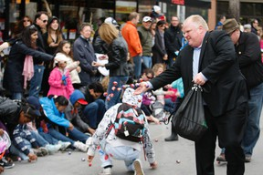 Mayor Rob Ford throws chocolate eggs to kids at the Beaches Easter Parade on Sunday. (CRAIG ROBERTSON, Toronto Sun)