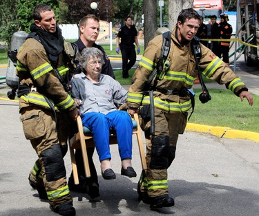 Edmonton Sun photographer David Bloom captured this moment when firefighters were carrying an elderly woman out on a kitchen chair from a fire at the Canora Gardens seniors home on Tuesday, July 31. Bloom snapped the shot as he was running to the scene. He says he got the call about the fire while photographing a news conference 50 blocks away. One resident died in the fire. (DAVID BLOOM/QMI AGENCY)