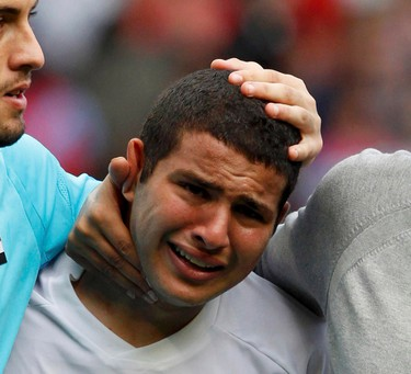 Coach Hany Ramzy (R) of Egypt walks with goalkeeper Mohamed Bassam and Eslam Ramadan (C) as he cries after their men's quarterfinal soccer match against Japan at the London 2012 Olympic Games at Old Trafford in Manchester, August 4, 2012.   REUTERS/Andrea Comas