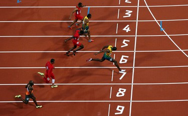 Jamaica's Usain Bolt (R) crosses the finish line to win  the men's 100m final during the London 2012 Olympic Games at the Olympic Stadium August 5, 2012.           REUTERS/Pawel Kopczynski