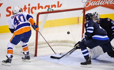 New York Islanders' Michael Grabner (L) scores on Winnipeg Jets' Ondrej Pavelec and Zach Bogosian (4) during the second period of their NHL hockey game in Winnipeg December 20, 2011. REUTERS/Fred Greenslade  (CANADA - Tags: SPORT ICE HOCKEY)