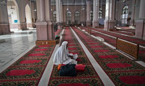 A man reads verses of the Qur'an on the second day of the holy month of Ramadan while sitting in the hall of Karachi's Memon Mosque on July 22, 2012. (REUTERS/Akhtar Soomro)