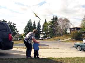 Residents watch a MNR waterbomber climbs into action. REG CLAYTON/Daily Miner and News