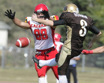 University of Manitoba Bisons kicker Brendon Bowman gets a punt away under pressure from University of Calgary Dinos player Adam Osterling during Canada West Conference football action at University Stadium on Sat., Sept. 15, 2012. JASON HALSTEAD/Winnipeg Sun