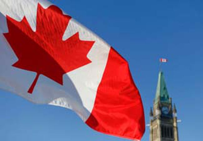 A Canadian flag waves in front of Parliament Hill in Ottawa. Chris Roussakis/QMI Agency