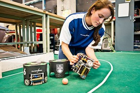 Mechanical engineering student Andrea Palmer toys with one of the UBC Thunderbots - autonomous soccer-playing robots - at a University of B.C. lab. (CARMINE MARINELLI/24 HOURS)