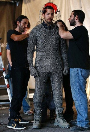 """Magician David Blaine is fitted with a metal suit and head cage before a demonstration of his upcoming performance """"Electrified"""" during a press briefing in New York, October 2, 2012. (REUTERS/Mike Segar)"""