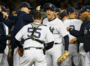 New York Yankees first baseman Mark Teixeira celebrates with catcher Russell Martin (55) after the Yankees defeated the Baltimore Orioles in Game 5 of their MLB ALDS baseball playoff series in New York, October 12, 2012. (REUTERS/Mike Segar)