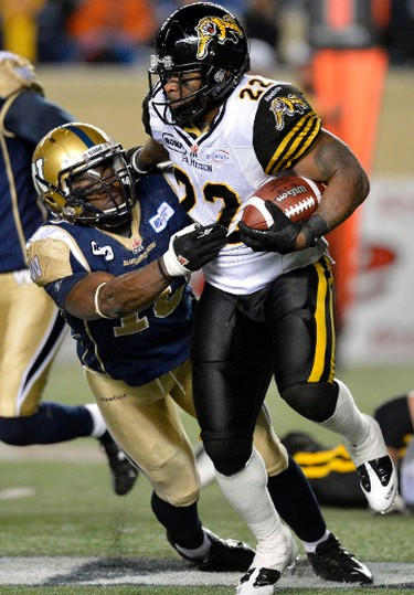 Hamilton Tiger-Cats' Avon Cobourne (R) is tackled by Winnipeg Blue Bombers' Henoc Muamba during the second half of their CFL football game in Winnipeg, September 21, 2012. REUTERS/Fred Greenslade (CANADA - Tags: SPORT FOOTBALL)