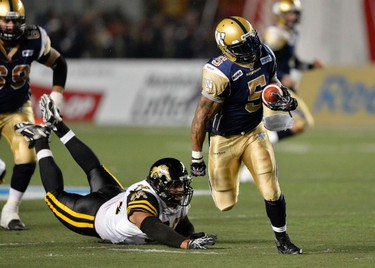 Winnipeg Blue Bombers' Chad Simpson (R) breaks away from Hamilton Tiger-Cats' Eddie Steele for a large gain during the second half of their CFL football game in Winnipeg, September 21, 2012. REUTERS/Fred Greenslade (CANADA - Tags: SPORT FOOTBALL)