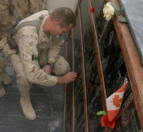 A soldier places a poppy on a plaque during  at the cenotaph Remembrance Day ceremonies at Kandahar Air Field.