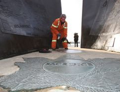 "A war memorial in Coronation Park was vandalized with black spray paint. City worker Margaret O'Brien sprays the words ""Canada will burn praise Allah"" with a chemical to remove them. (CRAIG ROBERTSON/Toronto Sun)"