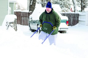 Brent Bobei clears snow out of his driveway on Sunday in Portage la Prairie.  City crews continue to make their rounds as they hope to fully complete snow removal on Tuesday.  (Jordan Maxwell/Portage Daily Graphic/QMI Agency)