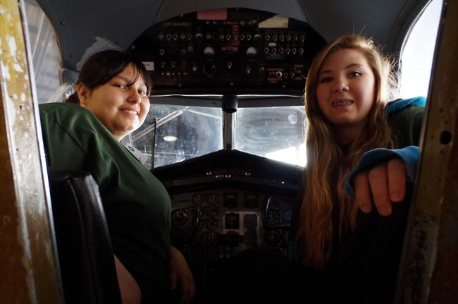 Melody Neveau, 18, and Nicole Woolsley, 17, sit in the cockpit of an airplane at the Canadian Bushplane Heritage Centre on Wednesday.