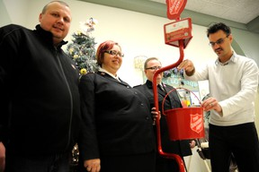 Adam Jackson/Daily Herald-Tribune Mayor Bill Given, right, makes the first donation to officially kick off the Salvation Army's Christmas kettle campaign Wednesday at the Family Service Centre on 102 Street. He is joined by co-ordinator Kerry Harris, left, Major Glenda Roode, and Major Daniel Roode.