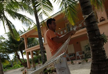 "Jose Najarro, 21, an employee of dead American businessman Gregory Faull, works outside of Faull's home in San Pedro November 14, 2012. Belizean police want to question anti-virus software pioneer John McAfee, 67, about the murder of his neighbor and fellow U.S. citizen, Gregory Viant Faull, 52, with whom McAfee had quarreled. Belize's prime minister on Wednesday urged McAfee to help the country's police with a murder inquiry, calling McAfee ""bonkers"" for recent media statements. REUTERS/Henry Romero"