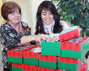 Gail Shillington and Paola Justiniano, an Bolivian exchange student at Providence Care Mental Health Services, fill a shoebox that will be delivered to children in Third World countries around the world.      Rob Mooy - Kingston This Week