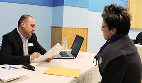 Applicant Elisa Kuuru-Goodman hands her application to John Crescenzi during Saturday's Holiday Inn job fair at Centre Cultural La Ronde Saturday. Thirty jobs are currently available at the hotel and staff expansion is planned over the next few months.