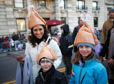 A family in turkey hats arrives to take a seat as the sun rises over the Macy's Thanksgiving Day Parade in New York, November 22, 2012.   REUTERS/Carlo Allegri