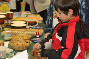 Aaron Lavoie, 8, was enjoying solving the artisan crafted puzzles Friday night at the Ten Thousand Villages Festival Sale.