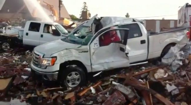 A volunteer firefighter starts up a beaten-up Ford F-150 and drives it over a pile of rubble left behind after Kelleher Ford was gutted by fire in September 2011.