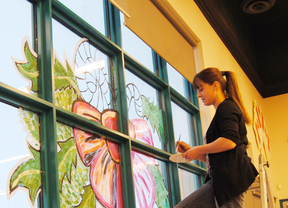 Kim Johner gets the Co-op ready for Christmas by decorating its front window on Monday, Nov. 19.