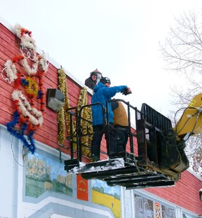 Fairview Rotary Members were putting up Christmas decorations on the old Fire Hall, Lenny Basnett up on the roof, Ken Thompson signalling to Perry Wild (not in photo) on the manlift while volunteer Keith Lyons finishes fastening a bolt securing the letters they were putting up. CHRIS EAKIN/FAIRVIEW POST/QMI AGENCY