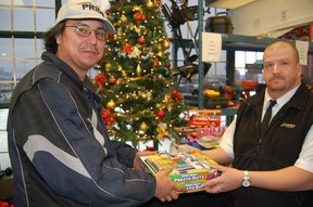 Lawrence Dashner hands over a toy donation to the Salvation Army's Peter Lewis at the Hock Shop on Saturday. Jonathan Migneault The Sudbury Star