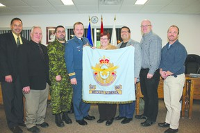 Members of council and the Cold Lake cadet squadron hold the old Medley flag, which will be donated to the museum.