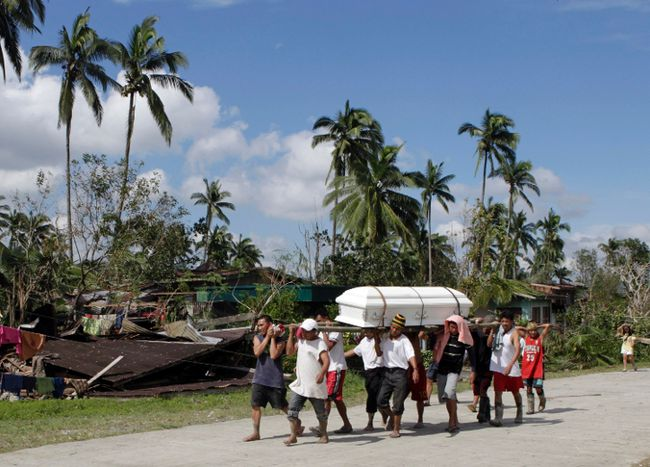 Residents carry the coffin of a typhoon victim past a destroyed house in New Bataan town in Compostela Valley in southern Philippines December 6, 2012. (REUTERS/Erik De Castro)