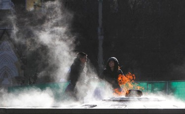 Tourists are seen in the  mist rising from the Centennial Flame on Parliament Hill in Ottawa Dec 6, 2012 as temperature fall in the capital city(ANDRE FORGET/QMI AGENCY)