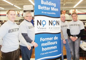 Building Better Men spread their message of healthy relationships on Saturday. Protius Grant, Ray Houde, Wayne McDermid and Dan O'Rourke show off the wristbands they handed out. Staff photo/KATHRYN BURNHAM