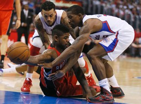 The Raptors' Amir Johnson is pressured by Los Angeles Clippers' Matt Barnes (left) and Eric Bledsoe on Sunday afternoon at the Staple Center. (Reuters)