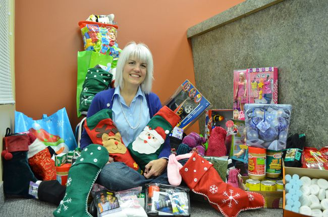Leslie Cassidy-Amadio looks pleased with the array of Christmas gifts she found at the Prince Township Municipal Office last week.  The items, donated to her JOYfull Socks campaign by Prince residents and firefighters, will go to make Christmas merrier for patrons of Soup Kitchen Community Centre, in Sault Ste. Marie.